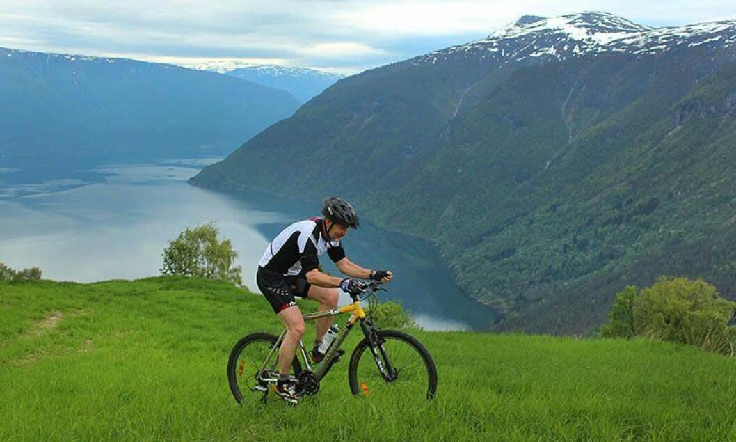 Arne Johannessen sykler i naturen rundt Hafslo.