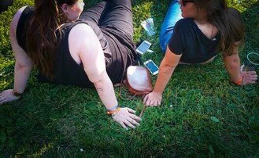 – Du kan prøve telle hvor mange som bare legger telefonene på gresset, sier den ene politimannen.