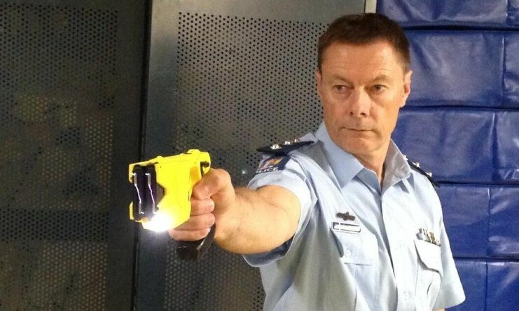 Politibetjent fra New Zealand viser fram elektrosjokkvåpen under en utstyrsdemonstrasjon.