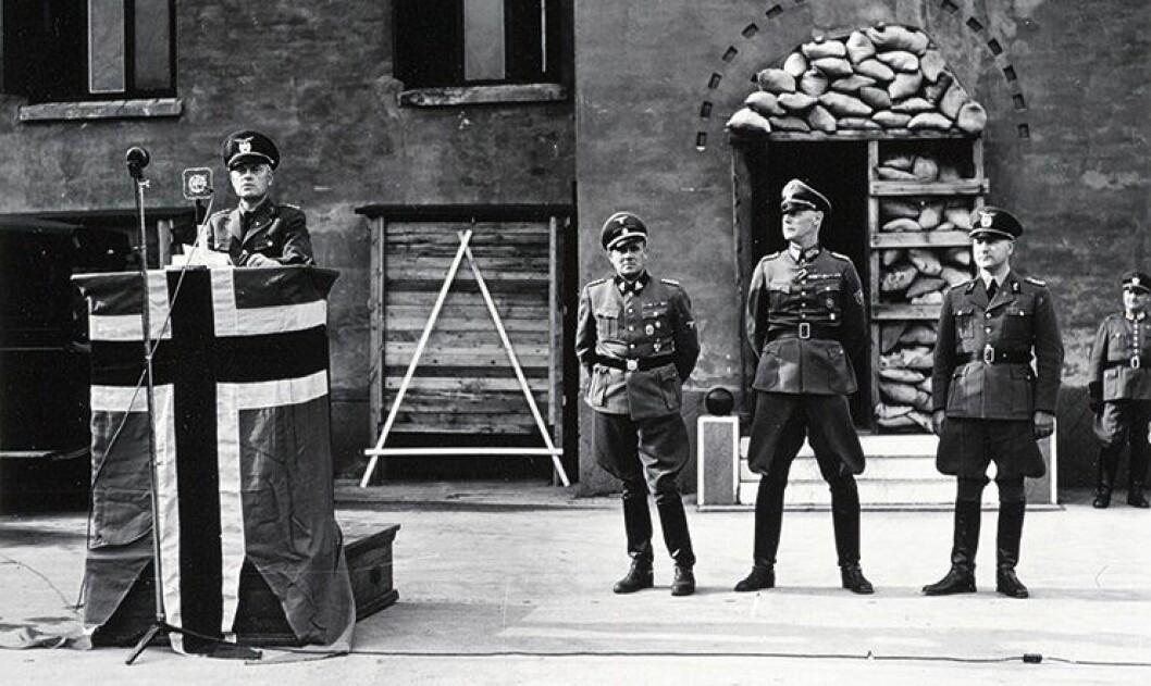 Talte: Politiminister Jonas Lie på talerstolen i påhør av blant annet Wilhelm Rediess.
