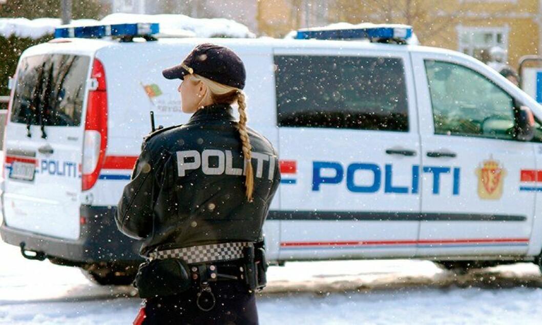 Politikvinne og politibil, vinter.