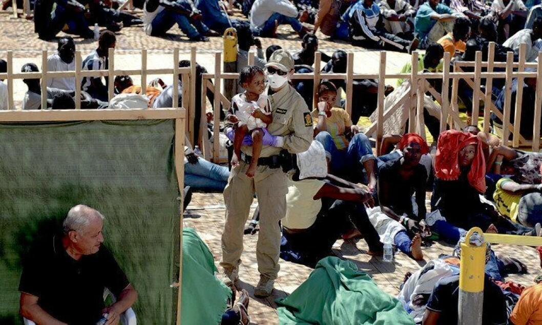 Trøst i varmen: Kristin Kjensberg plukker opp en av de yngste blant migrantene. KRistin jobbet i første rekke i mottaket og kom derfor tett innpå de desperate menneskene. Da kan det være godt å få litt menneskelig varme.