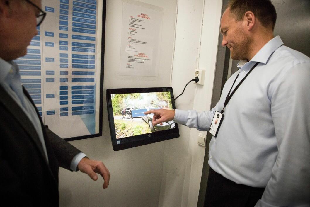 Harald Thorp og Cato Jakobsen viser fram det egenutviklede rapporteringsverktøyet, som er plassert utenfor garderoben.
