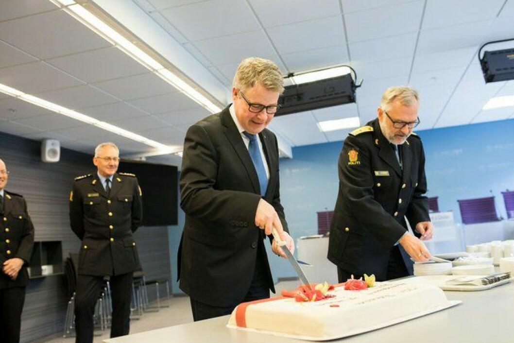 Smaken av nytt distrikt: Justisministeren og politimesteren var de to første til å smake på kaka som markerte det nye distriktets organisering. Politidirektøren fulgte nøye med.