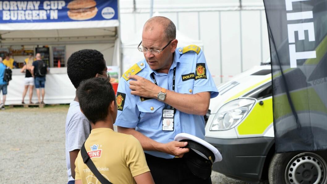NYSGJERRIGE BARN: Konstituert politimester i Oslo, Bjørn Vandvik, synes det var flott å kunne besøke Ekebergsletta. Her viser han frem stjernene på uniformen sin til to nysgjerrige gutter.