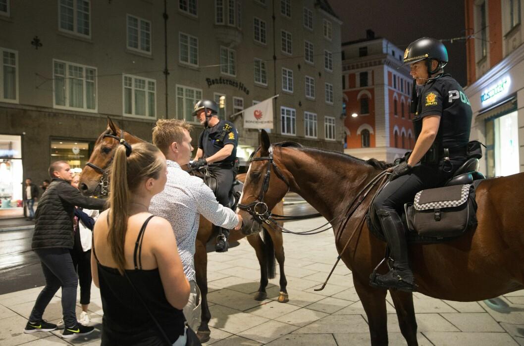 KONTAKTSØKENDE: Publikums ønske om å klappe hestene, innleder ofte til en samtale med politiet. Her får politihestene Balder og Hugin kos etter å ha gjort en jobb på Professor Aschehougs plass.