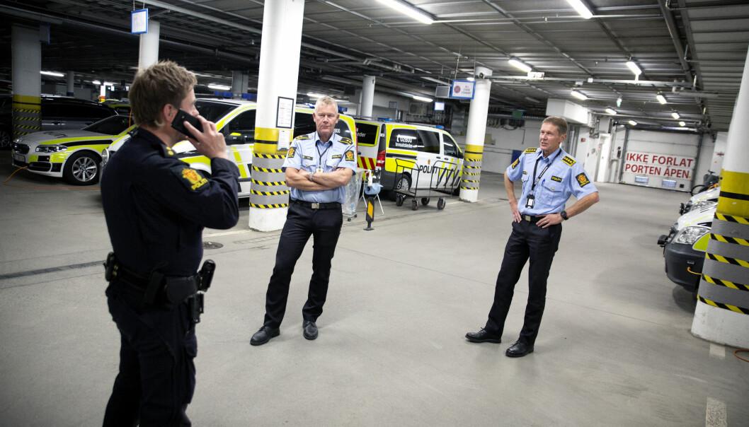 GRUNNPLAN: Stasjonssjef Arve Nordtvedt (til høyre) og kollega Torkjel Rendal (midten) i garasjen på Trondheim sentrum politistasjon. Politibetjent Helge Steinar Wengstad snakker i telefonen til venstre. – Jeg er bekymret for om disse nye stillingene blir fullfinansierte, sier Nordtvedt.