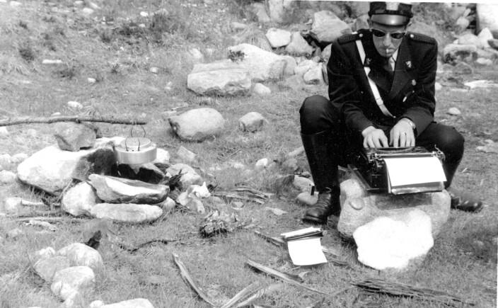 POLITIARBEID PÅ STEDET: Politikonstabel Lars Grøndal sitter på en stein og skriver rapport på en skrivemaskin ved veikanten i Østerdalen. Året er 1958.