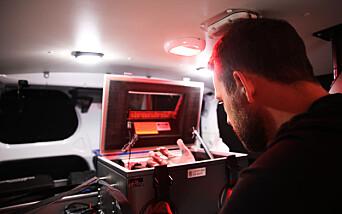 Politioverbetjent Anders Kjøde viser hvordan man kan jobbe med blant annet mobiltelefoner inne i Faraday-boksen. Hendene tres inn i et par hansker som er festet til boksen.