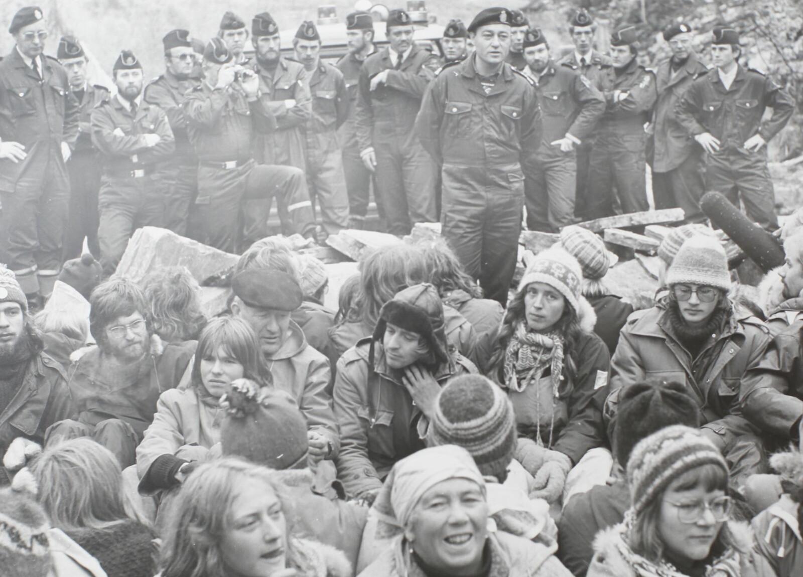 """<span class="""" font-weight-bold"""" data-lab-font_weight_desktop=""""font-weight-bold"""">TILBAKEBLIKK:</span> Høsten 1979 forsøkte det lokale politiet i Finnmark å bryte opp den første, store demonstrasjonen ved nullpunktet på Stilla. Lensmannsbetjent Knut Arvid Sætermo (bakerste rad, like til høyre for mannen som holder et kamera) var en av de 40-50 polititjenestemennene som kom til kort mot demonstrantene. Til slutt så politimester Einar Henriksen (stående nærmest demonstrantene, under) ingen annen utvei enn å avblåse aksjonen."""