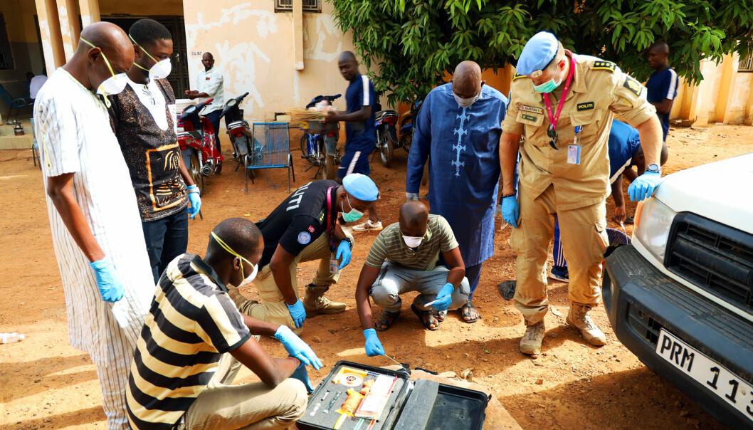 VÅPENÅSTED: Her veileder politimannen Rodrigue Nzyoibuka fra Vest politidistrikt en lokal kriminaltekniker i undersøkelse av et våpen. Politiinspektør Gustav Landro overvværer det hele.