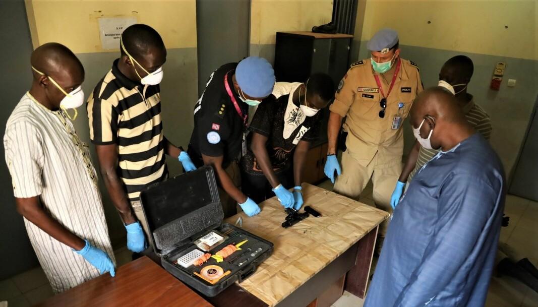 OPPLÆRING: Her viser politimannen Rodrigue Nzyoibuka og politiinspektør Gustav Landro (nummer tre og fem fra venstre) hvordan krimteknikere fra Malis best gjennomfører bevissikring av våpen.