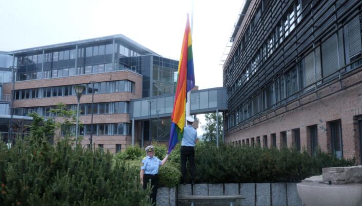 Kripos-sjef Kristin Kvigne og vaktleder på desken, Axel Johansen, heiser regnbueflagget utenfor Kripos.